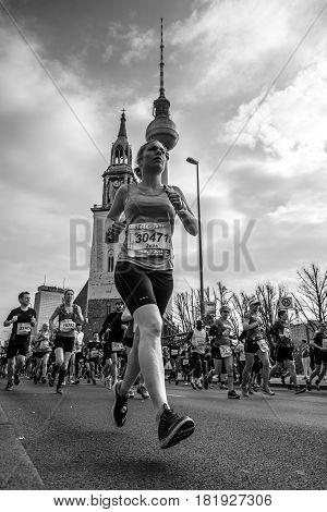 BERLIN - APRIL 02 2017: The annual 37th Berlin Half Marathon. Athletes run on Karl-Liebknecht-Strasse (Karl Liebknecht Street). Black and white.