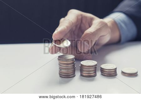 Business hand putting money coin stack growing business. Concept of investments and Saving money.Vintage tone