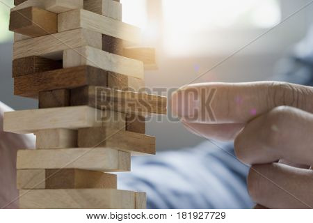 business man placing wooden block on a tower concept risk control Planning and strategy in business