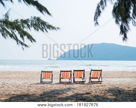 Four chaise lounges on beach