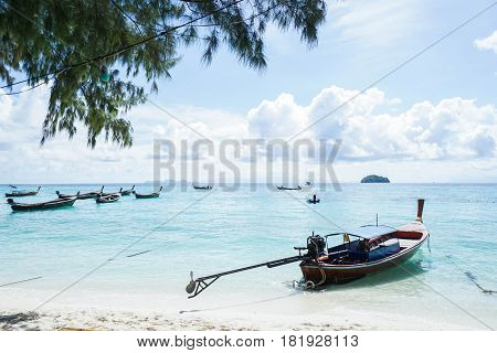 long tail boat on the deep blue sea shore with daylight