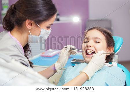 Close-up of pretty little girl opening his mouth wide during treating her teeth by the dentist.