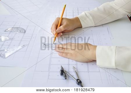 Close up Architect working on blueprint. Architects workplace - architectural working of Architect sketching a construction project on his plane project. Construction concept. Engineering tools