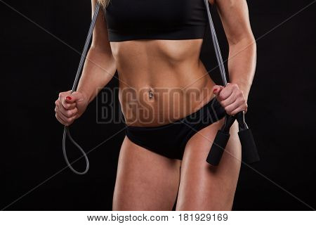 Beautiful fitness woman is holding a skipping rope, close view. Sporty girl showing her well trained body. isolated on dark background with copyspace.