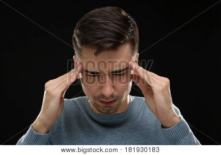 Handsome young man suffering from headache on black background