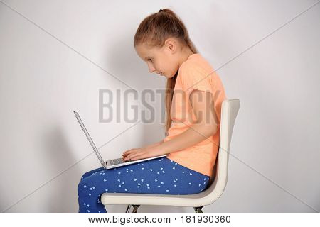 Incorrect posture concept. Cute schoolgirl with laptop sitting on chair