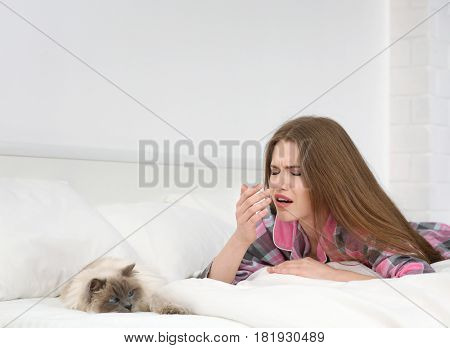 Animal allergy concept. Beautiful woman with cat in bed