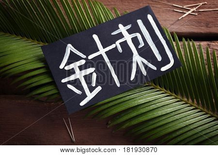 Card with word ACUPUNCTURE in chinese on leaf