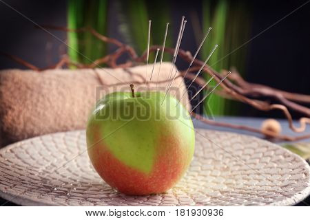 Apple with acupuncture needles on plate