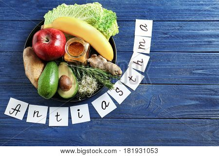Text ANTI ASTHMA and set of healthy products on wooden background