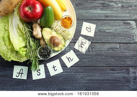 Text ASTHMA and set of products on wooden background