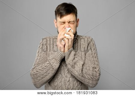 Young ill man on grey background