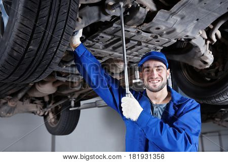 Young mechanic fixing wheel under car in  service