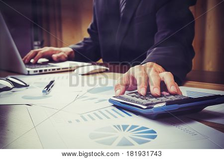 Asian Business Man Hand Pointing At Business Document During Discussion At Meeting And Using A Calcu