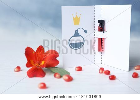 Beautiful composition with perfume sample in paper cover on blurred background