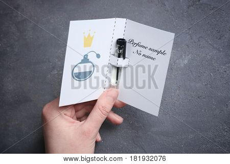 Female hand holding perfume sample in paper cover on gray background