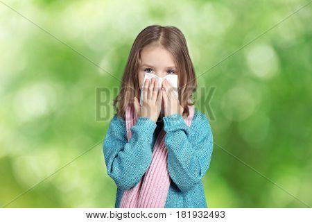 Seasonal allergy. Little girl with tissue on blurred background