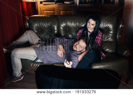 Couple of young tired people lay on couch and watch tv at home. Guy and girl bored from movie, changing channel with remote control.