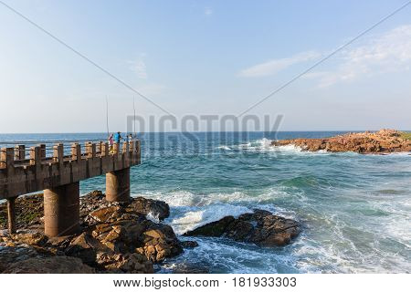 Beach ocean peir jetty with two fishing rods blue waters.