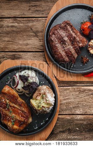 Traditional American delicious grilled beef steaks with garnish served on black plates, flat lay, free space. Menu photo.