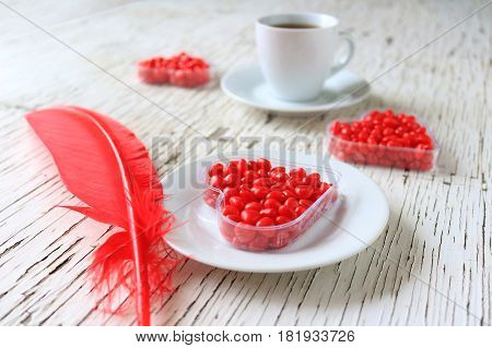 Red cinnamon hearts displayed with coffee and a red feather.