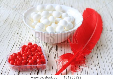 Red cinnamon hearts and mint candy displayed with a red feather.