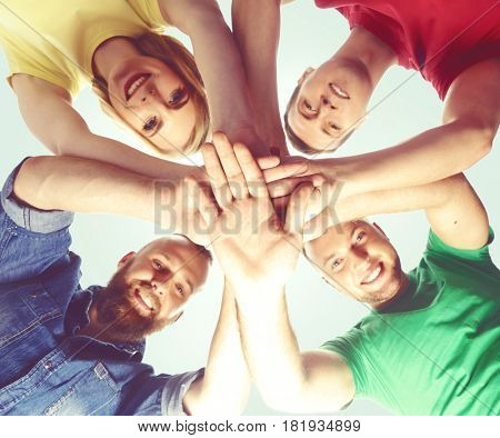 Group of happy friends staying together and looking at camera over blue background.