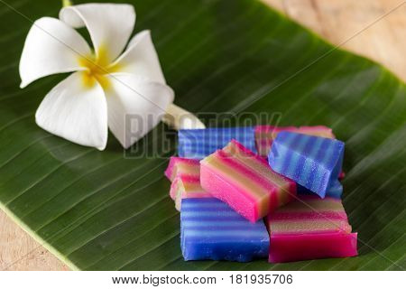 Name is Kanom Chan in Thailand. Put on banana leaf with Plumeria flower.