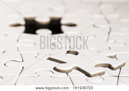still life with a white jigsaw over black background. business. problem solving. solution.