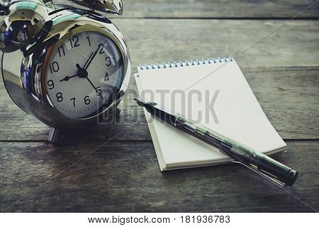 Time Management Concept: Vintage Tone Alarm Clock, Pen And Notepad On Old Wooden Table