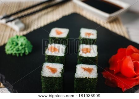 Appetising tasty sushi rolls set with delicious salmon served on black slate with ginger and wasabi. Japanese seafood.