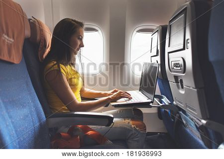 Woman using laptop while is sitting in plane near window