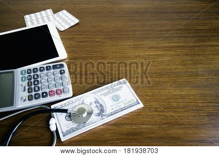 stethoscope on money whit calculator,digital tablet.The cost of healthcare concept