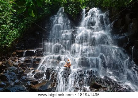 Travel in Bali jungle. Beautiful young woman sit in zen-like yoga pose under falling spring water enjoy tropic cascade waterfall. Nature day trip walking adventure fun on family summer vacation
