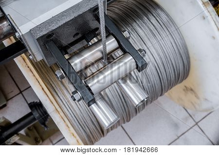 Manufacture of metal shielding braids for electrical cables. High-speed braiding machine. Winding the finished braid over the reel.