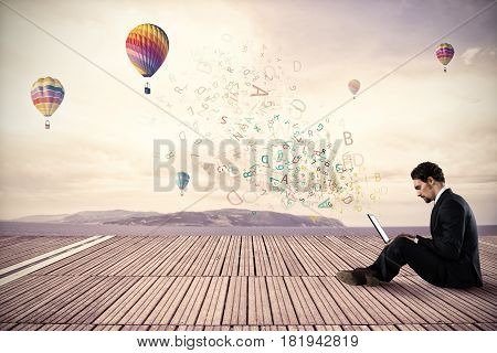 Businessman working with his laptop on background hot air balloons in the sky
