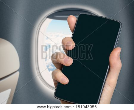 hand with blank mobile phone in airplane or jet interior