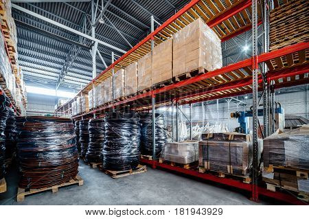 Warehouse transport and freight company. In the foreground a pile of cardboard boxes and a coil of plastic tubing. Toning the image.