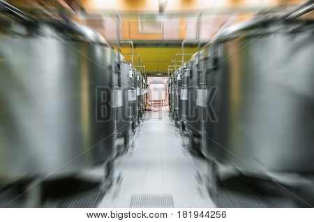 Modern Beer Factory. Rows of steel tanks for the storage and fermentation of beer. Motion blur effect