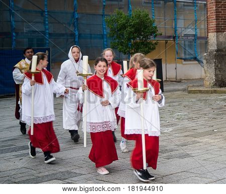 Neuoetting,Germany-April 16,2017: An altar girl smiles at the camera as she makes her way with other altar boys and girls to church for Easter Sunday mass.