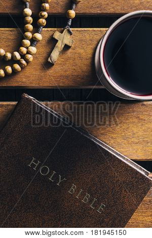 Rosary beads, holy bible and cup of wine on wooden table. Top view.