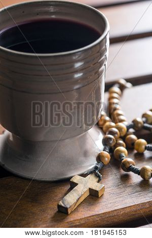 Rosary beads and cup of wine on wooden table.