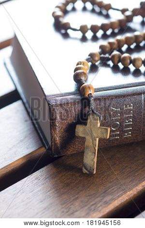 Rosary beads and holy bible on wooden table.