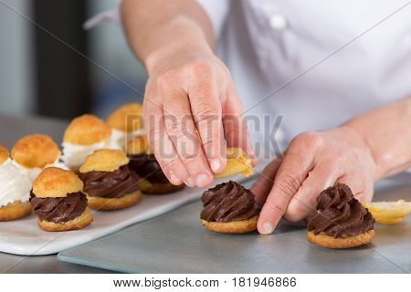 Chef confectioner finishing some delicious chocolate profiteroles