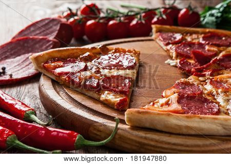 Junk food, bad habits. Pizza sliced on rustic wooden table background. Italian traditional meal, unhealthy eating, dining concept