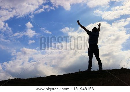 Man welcoming sunrise with raised hands concept of Spirituality and Inspiration
