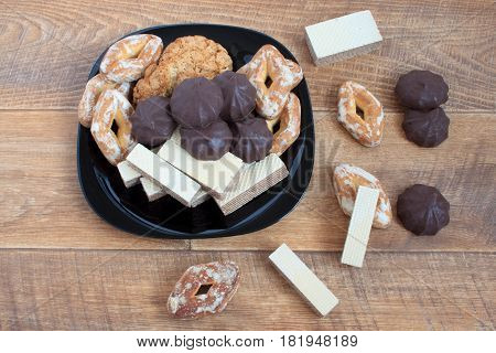 Marshmallow, spice-cake, and other sweets lying on the black plate. Isolated object on wood background.