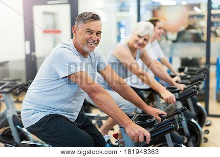 Confident seniors on exercise bikes