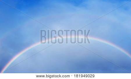 Colorful rainbow over cloud formations panoramic view