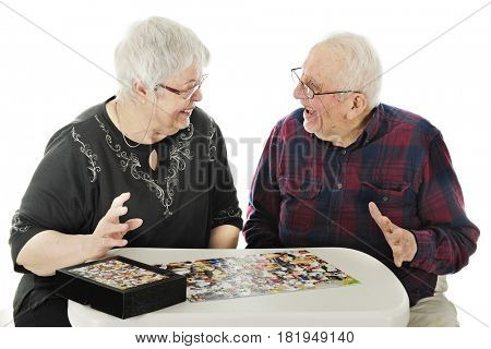 A senior adult couple delighted with themselves for completing a complicated jigsaw puzzle.  On a white background.